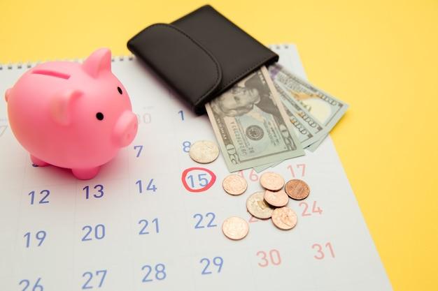 Es hora de invertir, concepto de negocio. rosa hucha y billetera con billetes de dinero, calendario sobre fondo amarillo.
