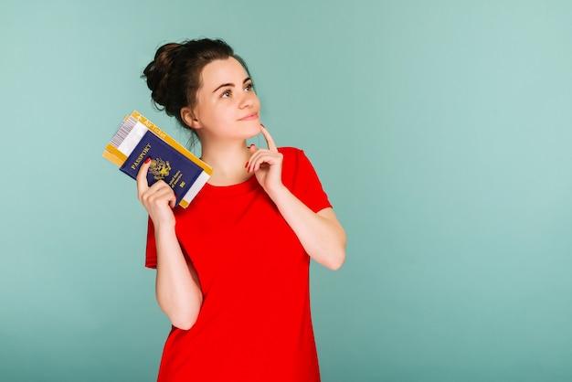 Es hora de viajar. una mujer sonriente de moda moderna en vestido rojo con billetes de avión y un pasaporte en la mano.