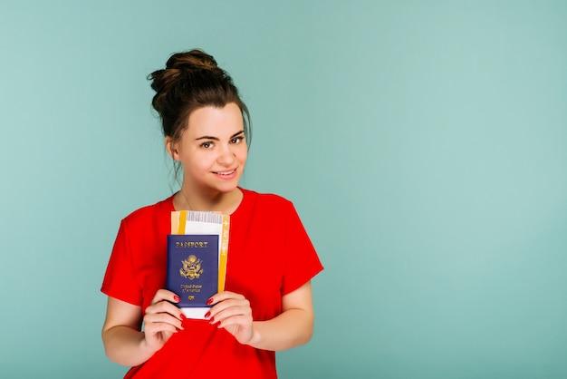 Es hora de viajar una mujer sonriente de moda moderna en vestido rojo con boletos de avión y un pasaporte en la mano