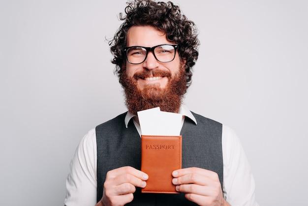 Es hora de viajar, trae tu pasaporte y vamos, hombre barbudo con gafas y mostrando entradas