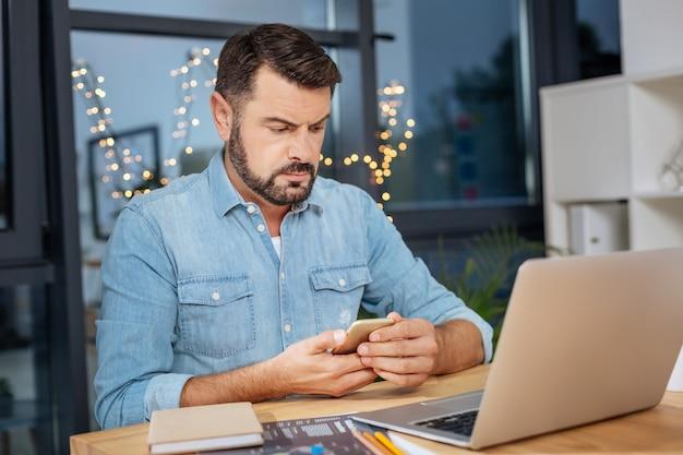 Esto es importante. hombre serio agradable con problemas sosteniendo un teléfono inteligente y revisando sus mensajes mientras está sentado frente a la computadora portátil