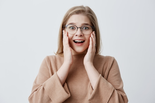 ¡es increíble! sorprendida, aturdida, emocional, mujer mantiene ambas manos en las mejillas, se sorprende al ver precios altos, aislada contra la pared del estudio en blanco. la mujer rubia no puede creer en noticias impactantes