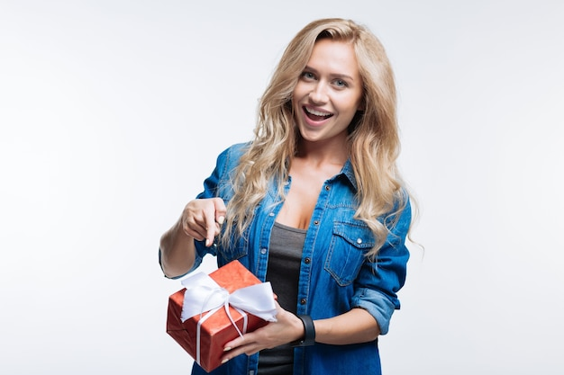 Esto es para ti. hermosa mujer joven sosteniendo una caja con presente y apuntando con su dedo mientras está de pie aislado sobre fondo gris