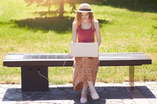 Esbelta chica atractiva que busca información en la red, carga portátil con ayuda de un panel solar construido en un banco de madera, aprovecha las ventajas de las nuevas tecnologías, está de buen humor. concepto ecológico.