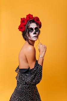 Esbelta chica de cabello oscuro con hermosa postura posando en vestido, mostrando los hombros. retrato de misteriosa dama mexicana con máscara de mascarada zombie