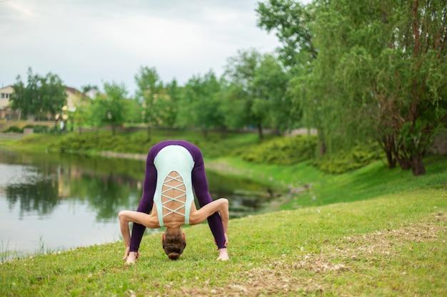 Esbelta chica morena caucásica haciendo yoga en verano en un césped verde junto al río