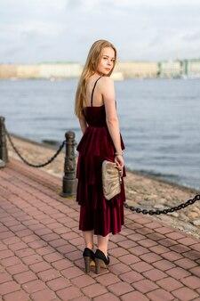 Esbelta chica rubia con un vestido hasta el tobillo burdeos mirando por encima del hombro en el terraplén.