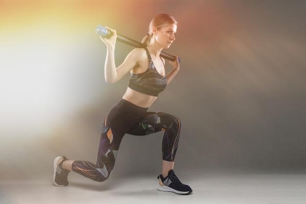 Esbelta chica en uniforme deportivo se lanza con un palo de gimnasia en una pared oscura con un efecto de brillo
