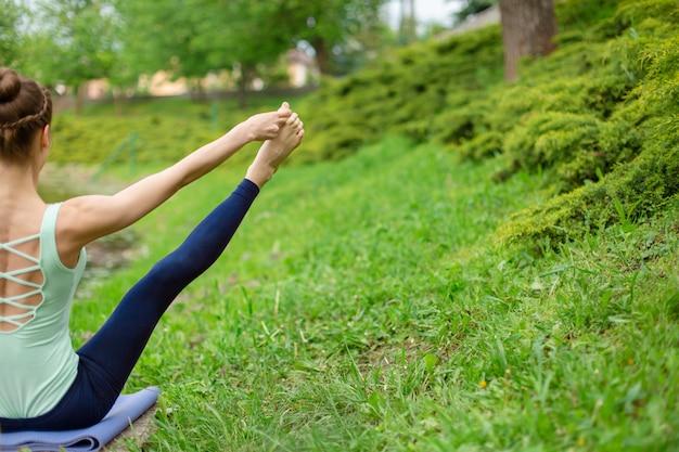 Esbelta joven morena yoga realiza desafiantes ejercicios de yoga en la hierba verde contra la naturaleza