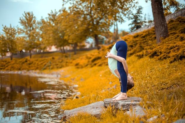 Esbelta joven morena yogui realiza desafiantes ejercicios de yoga en la hierba en otoño