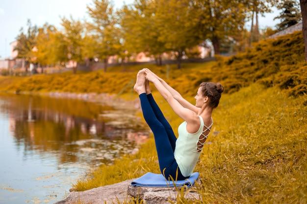 Esbelta joven yogui morena realiza desafiantes ejercicios de yoga en la hierba.