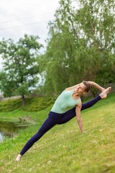 Esbelta joven yogui morena realiza ejercicio complejo de yoga en la hierba verde en verano