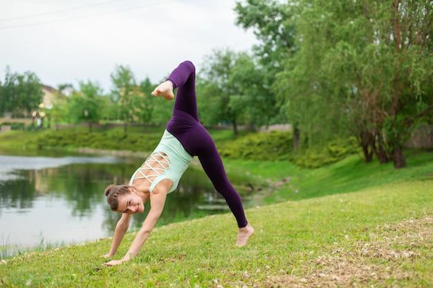 Esbelta joven yogui morena realiza ejercicio complejo de yoga en la hierba verde en el verano