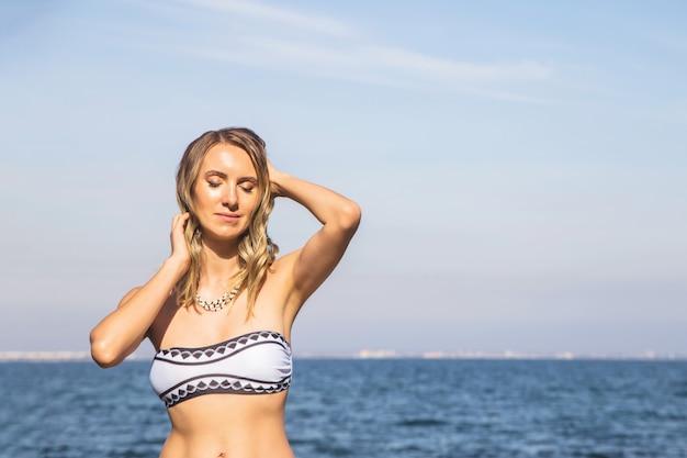 Esbelta niña caucásica en la playa junto al mar toma el sol en traje de baño.