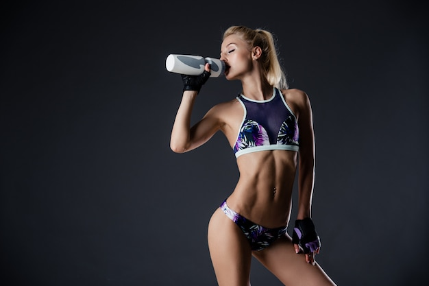 Esbelta niña deportiva agua potable, descansando después de ejercicios de fitness, cansado, copia espacio