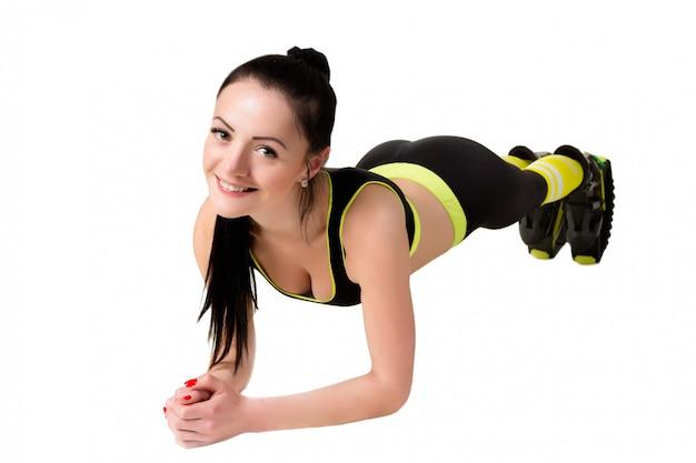 Esbelta niña sonriente en kangoo salta zapatos haciendo ejercicio tablón.