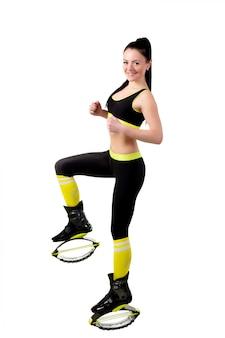 Esbelta niña sonriente en zapatos kangoo jamps haciendo ejercicios,
