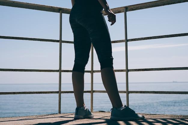 Esbeltas piernas de mujer en zapatillas azules y pantalones deportivos contra el mar temprano en la mañana