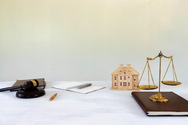Escala de bronce dorado con mazo y modelo de la casa. vivienda y derecho inmobiliario.