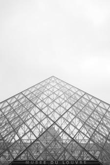 Escala de grises de ángulo bajo del museo del louvre bajo un cielo nublado en parís en francia
