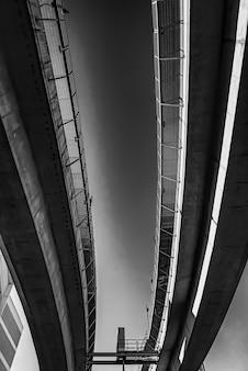 Escala de grises de ángulo bajo de un puente de hormigón bajo la luz del sol durante el día