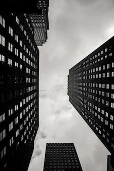 Escala de grises de ángulo bajo vertical de edificios de la ciudad con un cielo nublado en el fondo