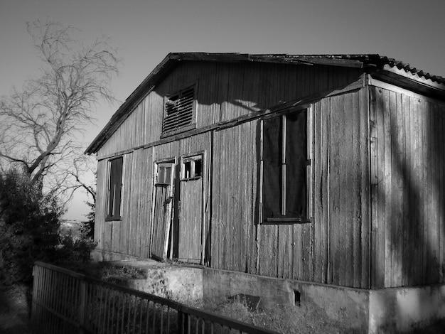 Escala de grises de un antiguo granero de madera bajo la luz del sol durante el día