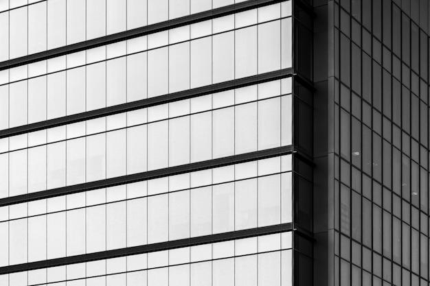 Escala de grises de un edificio moderno con ventanas de vidrio bajo la luz solar.