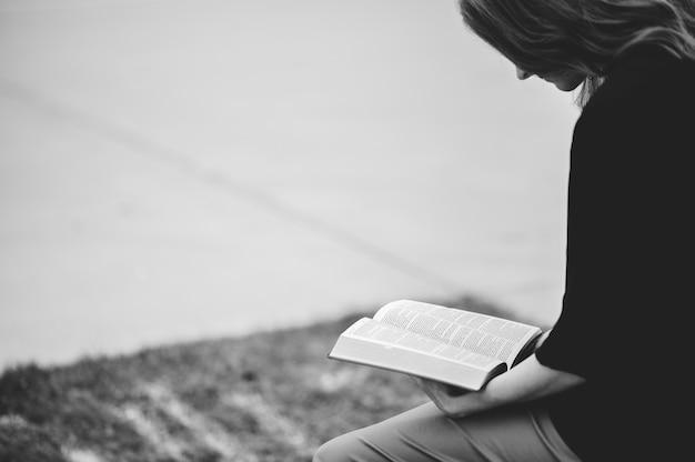 Escala de grises de una mujer sentada al aire libre mientras lee un libro