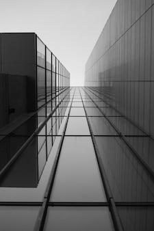 Escala de grises de un techo de un edificio moderno con ventanas de vidrio bajo la luz del sol