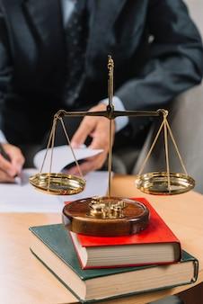 Escala de la justicia de oro en la pila de libros frente al abogado que firma el documento