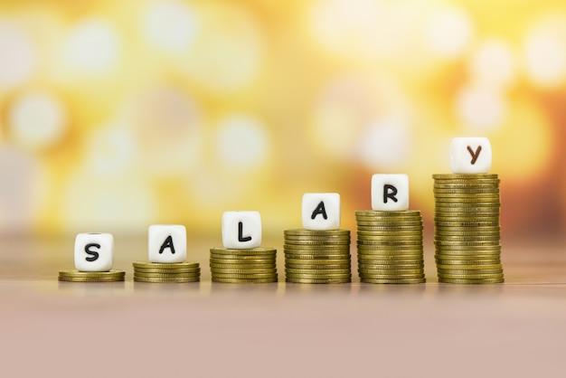 La escala de nómina y salarios aumenta el crecimiento de las monedas de dinero en la mesa y el concepto de éxito
