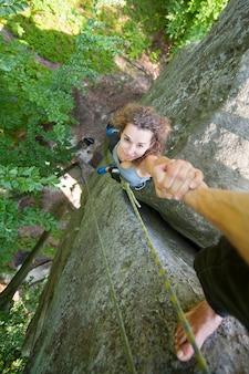 Escalador ayudando a escalador femenino a alcanzar un pico de montaña