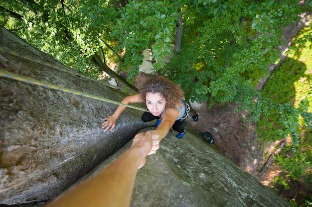 Escalador ayudando a escalador femenino a llegar a la cima de una montaña