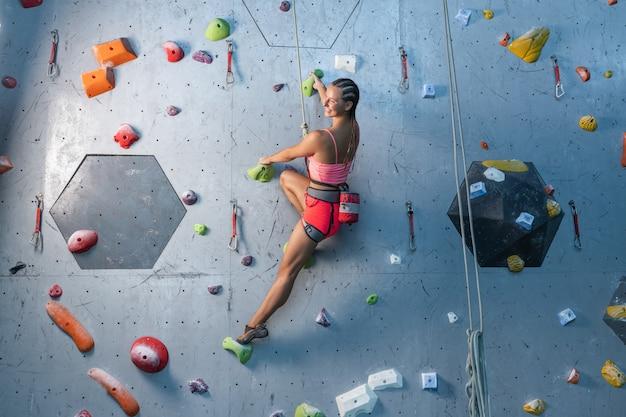 El escalador entrena en un relieve artificial. una mujer sube una ruta de escalada.