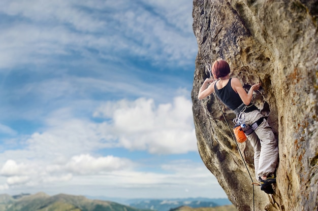 Escalador escalada con cuerda y carabinas en una gran pared rocosa