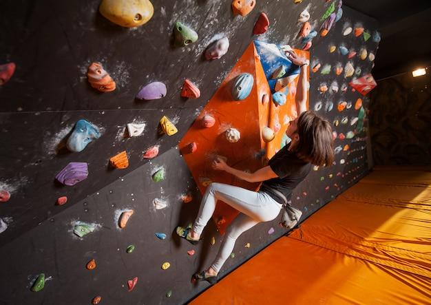 Escalador femenino fuerte en la pared de escalada boulder interior