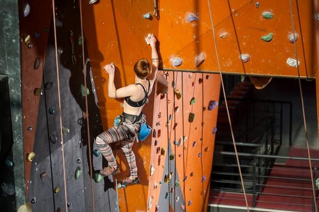 Escalador femenino joven atlético que practica la escalada en una pared de la roca dentro