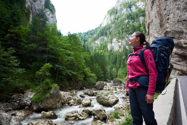 Escalador femenino positivo admirando la increíble vista de las verdes montañas rocosas cubiertas de hierba y la corriente de agua
