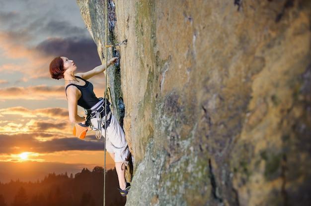 Escalador femenino que sube con la cuerda en una pared rocosa