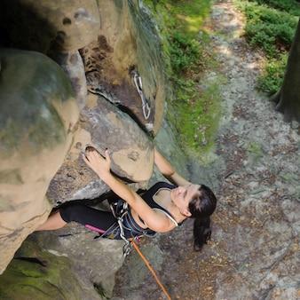 Escalador femenino que sube la roca grande en naturaleza con la cuerda