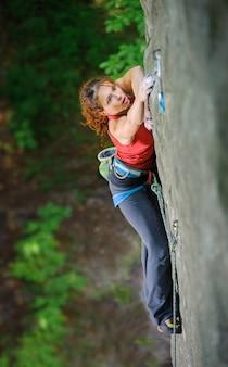 Escalador femenino subiendo roca empinada, en busca de agarre siguiente