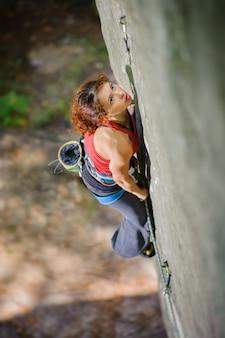 Escalador hermoso de la mujer que sube la roca escarpada con la cuerda