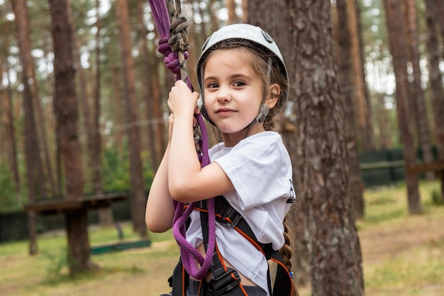 Escalador de la muchacha que cuelga en seguro en el bosque