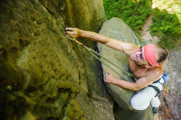 Escalador de roca masculino que sube con la cuerda en una pared rocosa