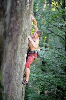 Escalador de roca muscular sube en acantilado que sobresale