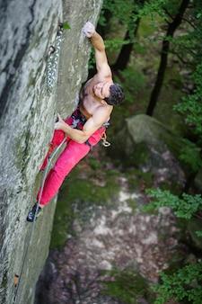 El escalador de roca muscular sube en el acantilado sobresaliente en tiempo de verano