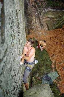 El escalador de roca muscular sube en la pared del acantilado con la cuerda