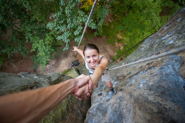 Escalador está sosteniendo una escaladora deportiva a mano en una pared rocosa