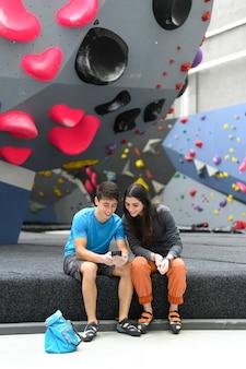 Escaladores con teléfono inteligente en el gimnasio de escalada
